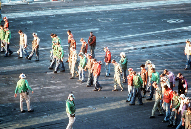 Sailors scan of the flight deck of the nuclear-powered aircraft carrier USS DWIGHT D. EISENHOWER (CVN-69) prior to the commencement of flight operations, searching for any debris that could cause foreign object damage (FOD) to aircraft operating on the deck. The EISENHOWER is in the region in support of Operation Desert Shield
