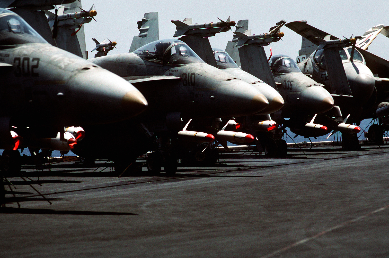 Strike Fighter Squadron 136 (VFA-136) F/A-18A Hornet aircraft and an Attack Squadron 34 (VA-34) A-6E Intruder aircraft, right, sit armed and ready on the flight deck of the nuclear-powered aircraft carrier USS DWIGHT D. EISENHOWER (CVN-69). The aircraft are armed with Mark 20 Rockeye II cluster bombs and AGM-88A HARM anti-radar missiles; the F/A-18 aircraft also carry AIM-9 Sidewinder missiles on their wing tips. The EISENHOWER is one of the U.S. Navy ships sent to the Persian Gulf in response to Iraq's invasion of Kuwait
