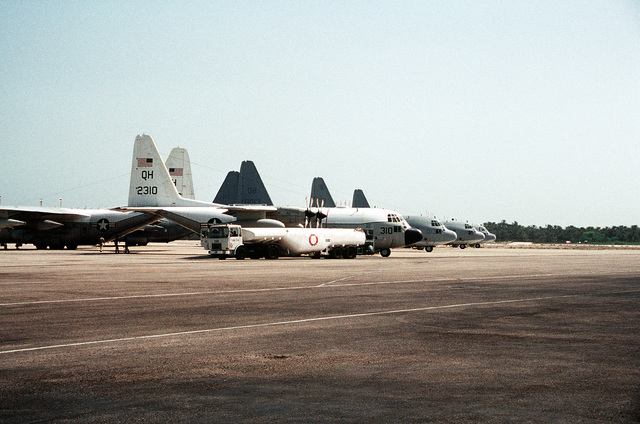 While parked on the flight line beside three KC-130 Hercules aircraft from Marine Refueler-Transport Squadron 352 (VMGR-352), a KC-130 Hercules aircraft from Marine Refueler-Transport Squadron 234 (VMGR-234), foreground, is loaded with fuel during Operation Desert Storm