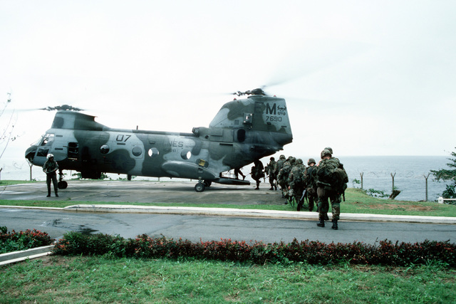 A squad of Marines boards a Marine Medium Helicopter Squadron 261 (HMM 261) CH-46E Sea Knight helicopter on the grounds of the US Embassy. Marines of the 22nd Marine Expeditionary Unit (22nd MEU), deployed aboard the amphibious assault ship USS SAIPAN (LHA 2), were sent to augment security at the embassy as part of Operation SHARP EDGE