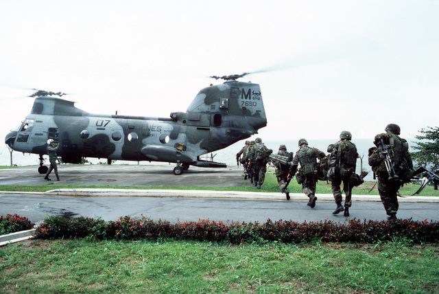 A squad of Marines moves to board a Marine Medium Helicopter Squadron 261 (HMM-261) CH-46E Sea Knight helicopter on the grounds of the United States Embassy. Marines of the 22nd Marine Expeditionary Unit (22nd MEU), deployed aboard the amphibious assault ship USS SAIPAN (LHA 2), were sent to augment security at the embassy as part of Operation SHARP EDGE