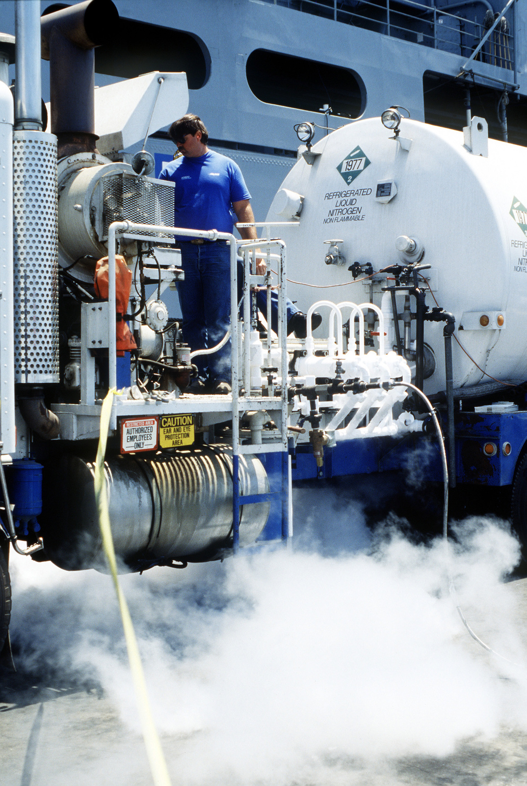 A worker operates the controls of a delivery truck as the nuclear-powered strategic missile submarine USS NEVADA (SSBN 733) takes on liquid nitrogen while undergoing maintenance at Long Beach Naval Shipyard