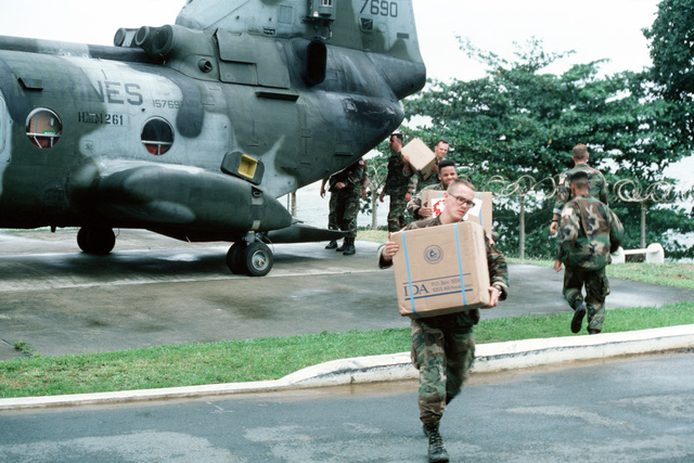 Marines unload boxes of supplies from a Marine Medium Helicopter Squadron 261 (HMM 261) CH-46E Sea Knight helicopter on the grounds of the US Embassy. Marines of the 22nd Marine Expeditionary Unit (22nd MEU), deployed aboard the amphibious assault ship USS SAIPAN (LHA 2), were sent to augment security at the embassy as part of Operation SHARP EDGE