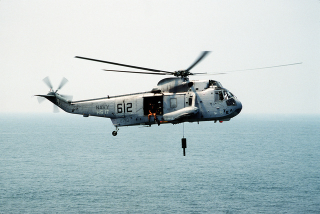A Helicopter Anti-submarine Squadron 17 (HS-17) SH-3H Sea King helicopter reels in its AQS-13B dipping sonar during a demonstration held as part of a dependents day cruise aboard the nuclear-powered aircraft carrier USS ABRAHAM LINCOLN (CVN-72)