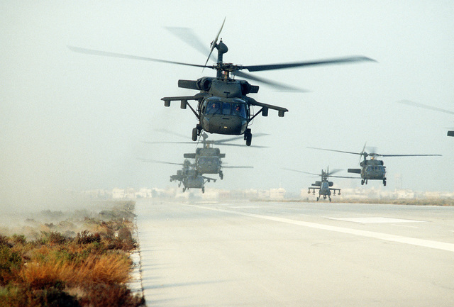 U.S. Army UH-60A Black Hawk (Blackhawk) helicopters and one AH-64A Apache helicopter, second from right, conduct a mass takeoff during Operation Desert Storm