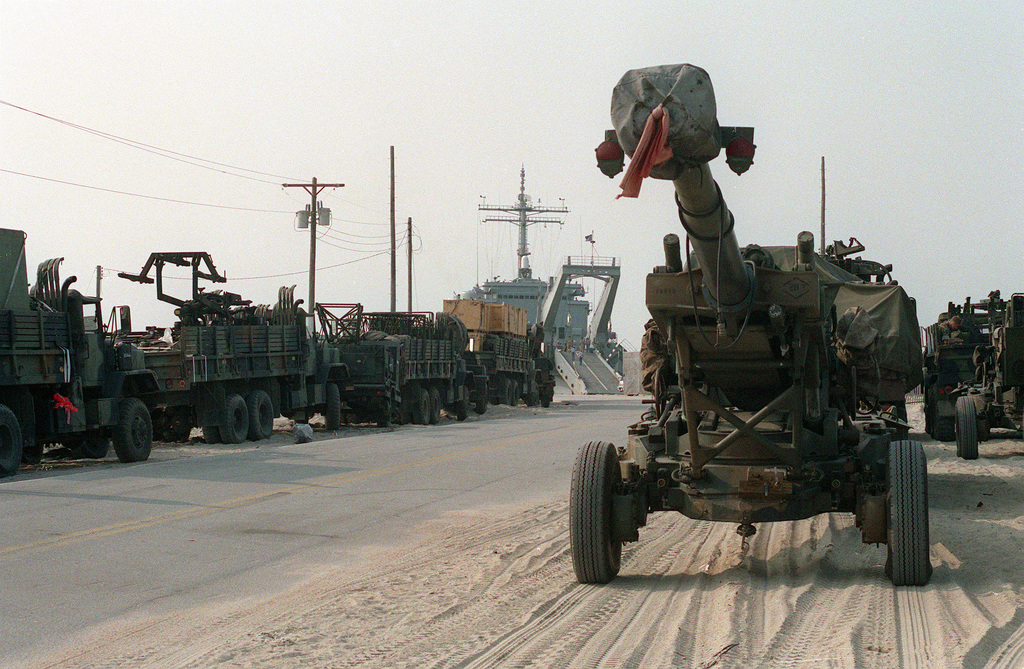 A Newport class tank landing ship is prepared to embark trucks and equipment of the 2nd Marine Division scheduled to participate in Operation Desert Shield. A 155mm M-198 howitzer is in the right foreground