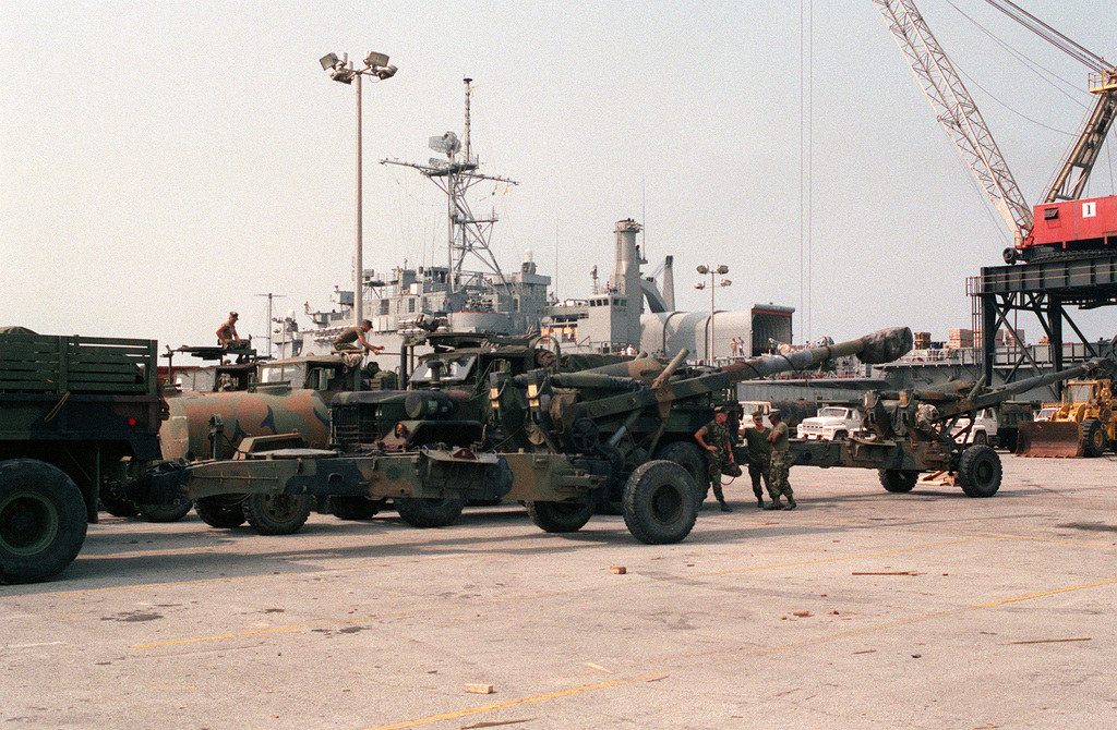 Marines relax around their gear while waiting to embark aboard Navy ships. Elements of the 2nd Marine Division are preparing to leave the U.S. to participate in Operation Desert Shield. A 155mm M-198 howitzer is in the foreground