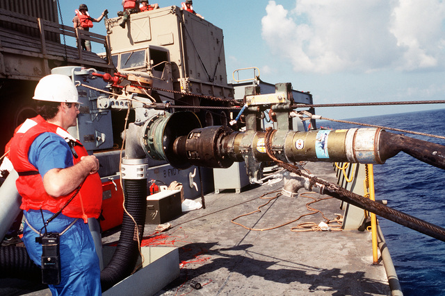A civilian crew member stands by alongside the refueling hose aboard the rapid-response vehicle cargo ship USNS REGULUS (T-AKR-292) as the vessel takes on fuel from the fleet oiler USNS TRUCKEE (T-AO-147). The REGULUS is en route to Saudi Arabia where it will offload equipment in support of Operation Desert Storm
