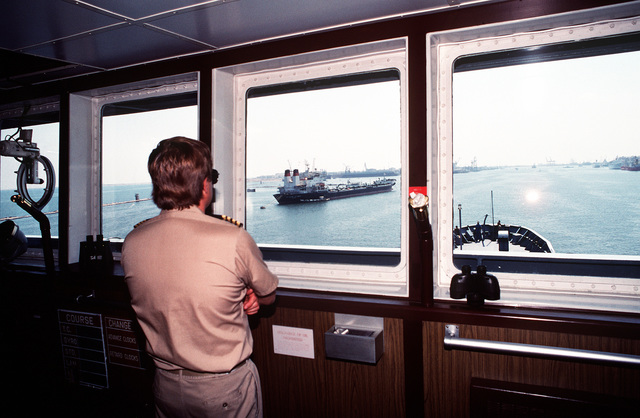 The captain looks out from the bridge of the rapid-response vehicle cargo ship USNS REGULUS (T-AKR-292) as the vessel transits the Suez Canal. The REGULUS is transporting equipment to Saudi Arabia in support of Operation Desert Storm