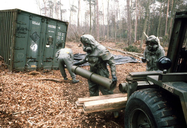 A member of a decontamination team picks up a metal canister used to store leaking chemical artillery rounds as the cleanup of a contaminated area begins during Operation CROCODILE, a training exercise for medical, decontamination and chemical reaction team personnel