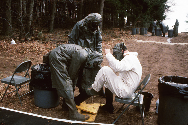 A soldier wearing a nuclear-biological-chemical (NBC) protective suit and mask helps a fellow soldier remove his protective boots at a personnel decontamination station during Operation Crocodile, a training exercise for medical, decontamination and chemical reaction team personnel