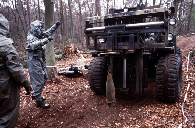 A soldier wearing nuclear-biological-chemical (NBC) protective suit and mask directs the driver of a forklift as a simulated chemical artillery round is brought in for disposal during Operation CROCODILE, a training exercise for medical, decontamination and chemical reaction team personnel
