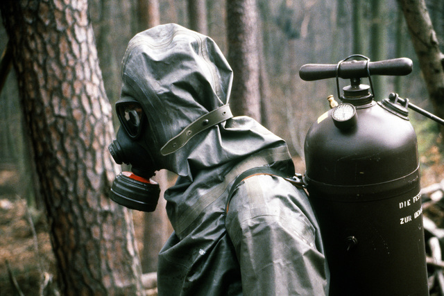 A West German soldier wearing a nuclear-biological-chemical (NBC) protective suit and mask carries a tank of decontamination solution on his back during Operation CROCODILE, a training exercise for medical, decontamination and chemical reaction team personnel
