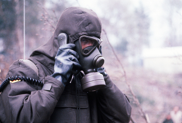 A West German soldier wearing a nuclear-biological-chemical (NBC) protective suit and mask talks on a field telephone during Operation Crocodile, a training exercise for medical, decontamination and chemical reaction team personnel
