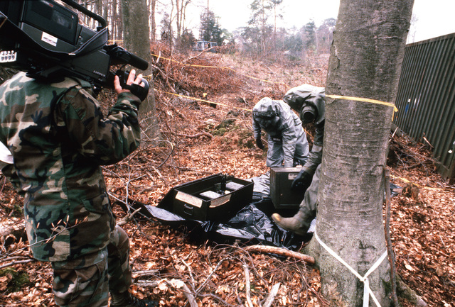 As an Army video cameraman films their activities, a decontamination team stages boxes of gear on a plastic sheet before beginning their cleanup of an area during Operation CROCODILE, a training exercise for medical, decontamination and chemical reaction team personnel