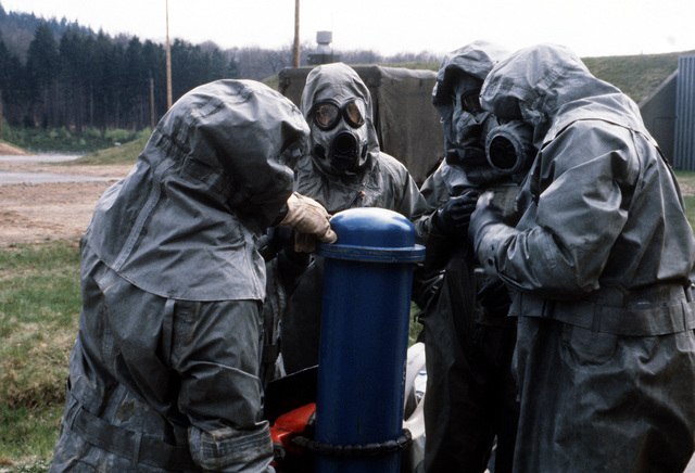 Chemical reaction team personnel wearing nuclear-biological-chemical (NBC) protective suits and masks seal a canister after placing a simulated chemical artillery round inside during Operation CROCODILE, a training exercise for medical, decontamination and chemical reaction team personnel