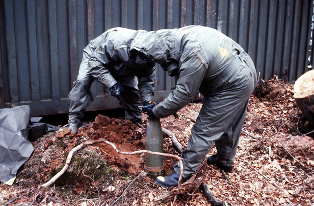 Members of a decontamination team place a simulated chemical artillery round in a buried metal canister to prevent further contamination during Operation CROCODILE, a training exercise for medical, decontamination and chemical reaction team personnel