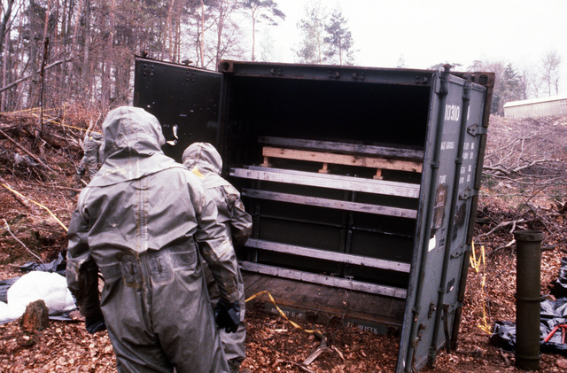 Members of a decontamination team prepare a container to receive canisters of simulated chemical artillery rounds during Operation CROCODILE, a training exercise for medical, decontamination and chemical reaction team personnel