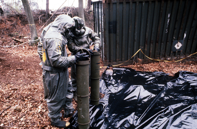 Members of a decontamination team seal up two metal canisters containing simulated chemical artillery rounds during Operation CROCODILE, a training exercise for medical, decontamination and chemical reaction team personnel