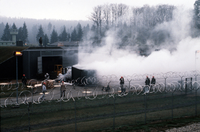 Smoke grenades are ignited to simulate an exploded chemical artillery round at a chemical weapons storage site during Operation CROCODILE, a training exercise for medical, decontamination and chemical reaction team personnel