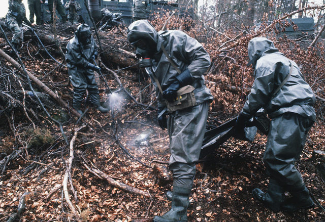 West German soldiers wearing full Nuclear-Biological-Chemical (NBC) protective suits and masks decontaminate the area around a simulated chemical artillery round before disposing of the round during Operation Crocodile, a training exercise for medical, decontamination and chemical reaction team personnel