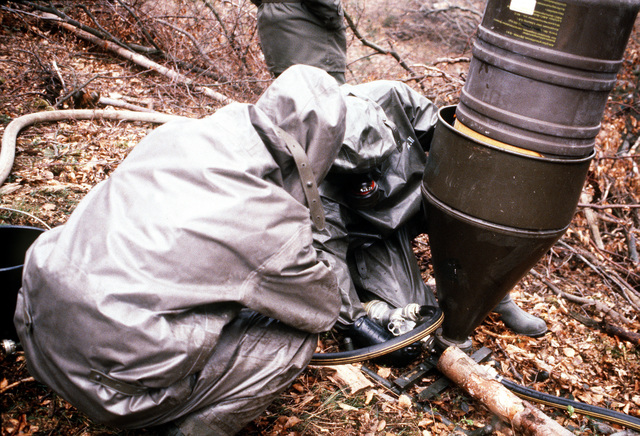West German soldiers wearing nuclear-biological-chemical (NBC) protective suits and masks prepare a decontamination solution during Operation CROCODILE, a training exercise for medical, decontamination and chemical reaction team personnel