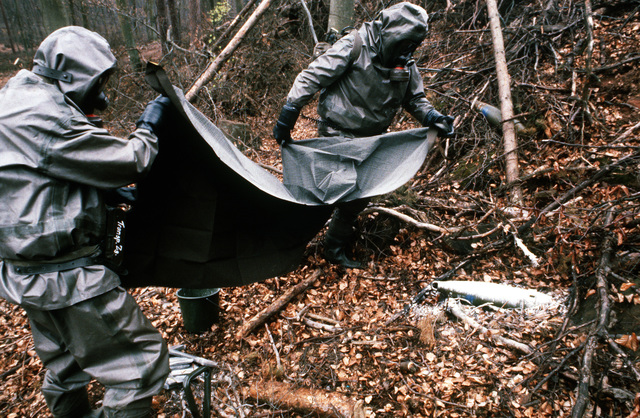 West German soldiers wearing nuclear-biological-chemical (NBC) protective suits and masks cover a simulated chemical artillery round with a sheet after coating it with a decontaminant during Operation CROCODILE, a training exercise for medical, decontamination and chemical reaction team personnel