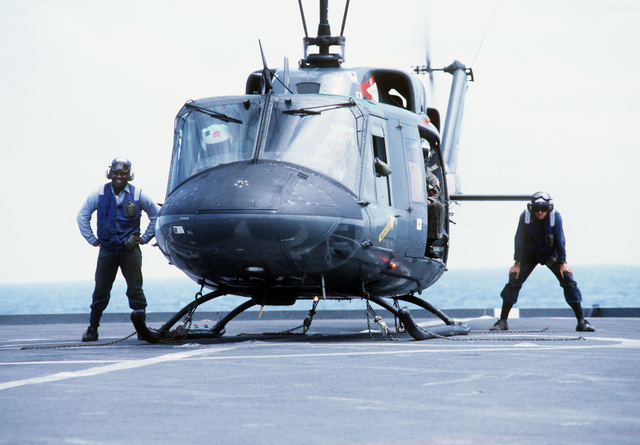 Two flight deck crewmen stand by to remove the tie-down chains from a UH-1N Iroquois helicopter aboard the dock landing ship USS WHIDBEY ISLAND (LSD-41) during Operation Sharp Edge. The Whidbey Island is part of an amphibious ready group that is in place off the coast of Liberia to provide support for the U.S. Embassy in Monrovia, Liberia, and evacuate civilians caught in that country's civil war