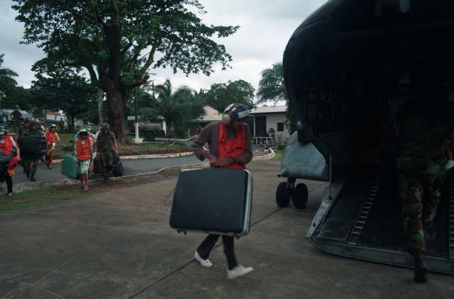 A man fleeing Liberia's civil war carries his suitcase onto a Marine Corps Ch-46E Sea Knight helicopter on the grounds of the U.S. Embassy during Operation Sharp Edge. The helicopter will carry a group of evacuees to one of the ships of an amphibious ready group on station off the Liberian coast. The ready group is also providing personnel and logistic support for the embassy