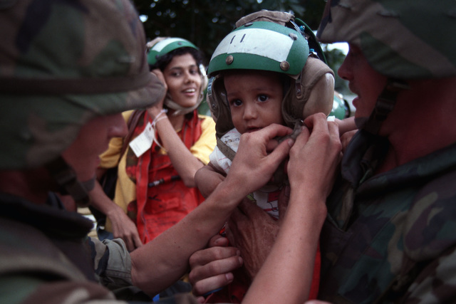 A Marine buckles the chin strap on a child's cranial helmet before a group of evacuees boards a Marine Corps helicopter on the grounds of the U.S. Embassy during Operation Sharp Edge. The evacuees, who are fleeing the civil war in Liberia, were first processed aboard one of the ships of an amphibious ready group that is on station off the Liberian coast