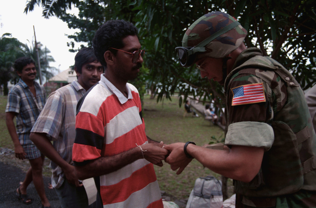 A Marine checks the manifest ticket of a man waiting to board a helicopter on the grounds of the U.S. Embassy during Operation Sharp Edge. An amphibious ready group on station off the Liberian coast is providing support for the embassy and assisting in the evacuation of civilians fleeing Liberia's civil war