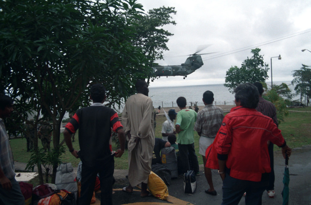 Civilians fleeing Liberia's civil war watch as a Marine Medium Helicopter Squadron 162 (HMM-162) CH-46E Sea Knight helicopter lands at the U.S. Embassy during Operation Sharp Edge. The helicopter will carry a group of evacuees to one of the ships of an amphibious ready group on station off the Liberian coast. The ready group is also providing personnel and logistic support for the embassy
