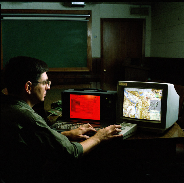 SSGT Norm McDonald uses an aircraft mission planning system at a computer display terminal