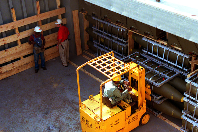 A workman uses a forklift to move pallets of Mark 84 2,000-lb. bombs in the cargo hold of a barge. The bombs are part of an ordnance shipment bound for the Middle East in support of Operation Desert Shield
