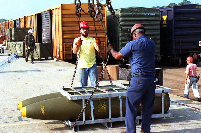Workmen adjust cables on a pallet of Mark 84 2,000-lb. bombs, part of an ordnance shipment bound for the Middle East in support of Operation Desert Shield