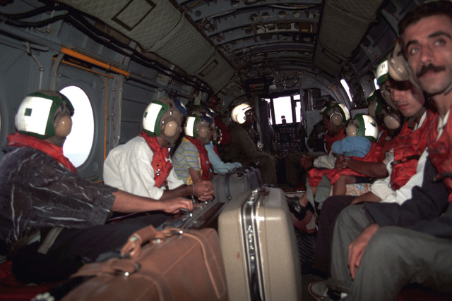 Evacuees sit aboard a Marine Medium Helicopter Squadron 162 (HMM-162) CH-46E Sea Knight helicopter while en route to Freetown, Sierra Leone, during Operation Sharp Edge. The evacuees, who are fleeing the civil war in Liberia, were first processed aboard one of the ships of an amphibious ready group that is on station off the Liberian coast