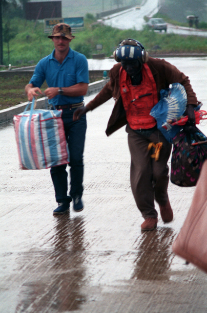 An American serviceman in civilian clothes helps a man with his bags at the Lungi Airport, just north of Freetown, Sierra Leone, after the arrival of a helicopter loaded with evacuees during Operation Sharp Edge. The civilians, who were evacuated from the midst of the civil war in Liberia, were processed aboard a U.S. Navy ship off the coast of Liberia before being flown to Sierra Leone