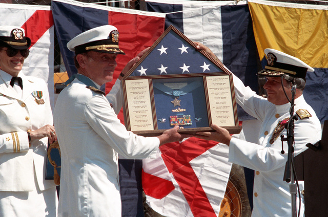Captain Thomas G. Kelley and Vice Admiral Jeremy Boorda, CHIEF of Naval Personnel, Deputy of Naval Operations (manpower, personnel and training), hold up a plaque presented to Kelley during his retirement ceremony at the United States Navy Memorial. During his distinguished naval career, Kelley received numerous awards, including the Medal of Honor for conspicuous gallantry while serving in Vietnam
