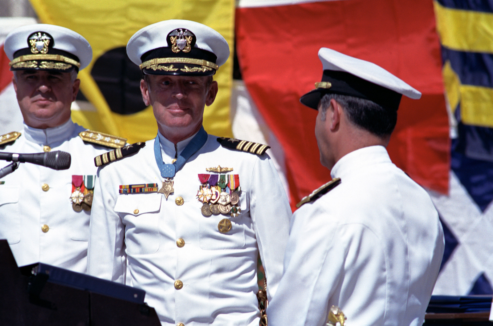 Rear Admiral Alvin B. Koeneman, CHIEF of Chaplains/Director of Religious Ministeries, stands by as an officer speaks with Captain Thomas G. Kelley during the captain's retirement ceremony at the United States Navy Memorial. During his distinguished naval career, Kelley received numerous awards, including the Medal of Honor for conspicuous gallantry while serving in Vietnam