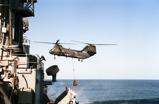 During vertical replenishment, an HH-46 Sea Knight helicopter of Helicopter Combat Support 5 (HC-5) from the Military Sealift Command combat stores ship USNS SPICA (T-AFS-9) transfers provisions to the guided missile destroyer USS GOLDSBOROUGH (DDG-20) during Operation Desert Storm