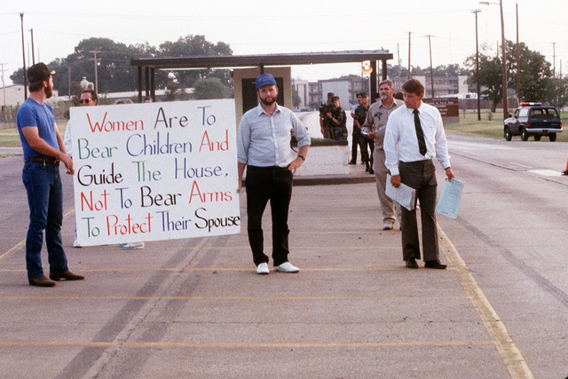 Local minister Rev. R.N. Otwell, right, and his followers stage a protest outside the main gate. Otwell's group believe that women should not be allowed to serve in the military. The protestors particularly object to the role of women in Operation Desert Shield