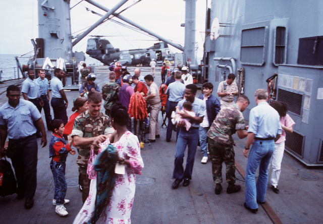 Marines conduct a quick check of the contents of bags brought aboard the tank landing ship USS BARNSTABLE COUNTY (LST 1197) by civilians flown onto the ship during Operation Sharp Edge. Civilians are being brought aboard U.S. Navy ships off the coast of Liberia after being evacuated from the midst of that country's civil war
