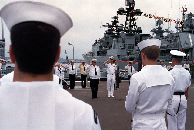 Admiral Gennadi Khvatov, center left, Commander, Soviet Pacific Fleet, and Admiral Charles R. Larson, Commander in CHIEF, US Pacific Fleet, salute as the colors are paraded at a review held during a visit to Vladivostok by two US Navy ships. The guided missile cruiser USS PRINCETON (CG 59) and the guided missile frigate USS REUBEN JAMES (FFG 57) are in the city for four days as part of a goodwill exchange program