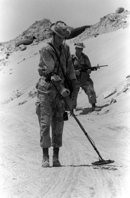 A Marine uses a hand-held mine detector while taking part in an exercise near the 3rd Marine Regiment's Combat Operations Center (COC) during Operation Desert Shield.
