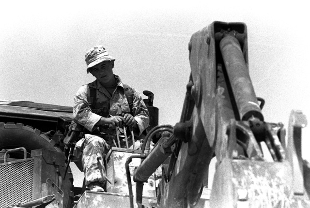 A Marine uses the backhoe on the rear of a small emplacement excavator (SEE) to dig a trench at the 3rd Marine Regiment's combat operations center (COC) during Operation Desert Shield.