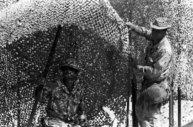 Two Marines erect a camouflage net at the 3rd Marine Regiment's combat operations center (COC) during Operation Desert Shield.