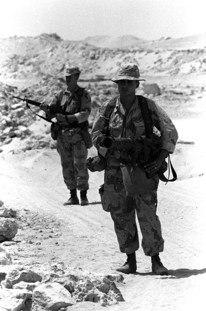Two Marines patrol along a road while participating in an exercise near the 3rd Marine Regiment's combat operations center (COC) during Operation Desert Shield. The Marine in the foreground is carrying a shoulder-launched multipurpose assault weapon (SMAW).