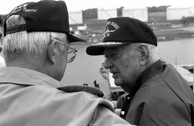 Retired Admiral Arleigh A. Burke, namesake of the guided missile destroyer ARLEIGH BURKE (DDG 51), converses with Vice Admiral John W. Nyquist, Assistant CHIEF of Naval Operations, Surface Warfare, as the ship docks in port following sea trials