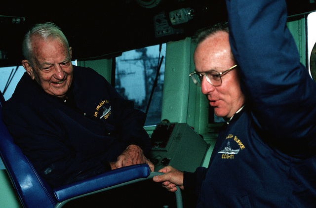 Retired Admiral Arleigh A. Burke, namesake of the guided missile destroyer ARLEIGH BURKE (DDG 51), stands on the ship's deck with his grandson, Dr. Pat Ward, as the vessel travels down river for sea trials off the coast of Maine. The ARLEIGH BURKE is one of the few ships that has ever been named for a living person
