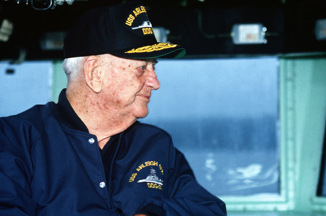 Retired Admiral Arleigh A. Burke, namesake of the guided missile destroyer ARLEIGH BURKE (DDG 51), looks out from the ship's bridge as the vessel heads down river for sea trials off the coast of Maine. The ARLEIGH BURKE is one of the few ships that has ever been named for a living person